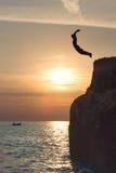 Vrije jongen die in de hemel door van de klip vliegen te springen stock foto's