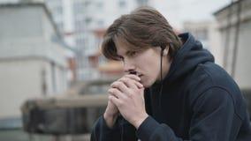 Vrije mens die zorgvuldig aan de muziek in oortelefoons op een dak luisteren stock footage