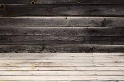 Vrije ruimte boven de houten oppervlakte van horizontale raad tegen de achtergrond van een donkere houten muur De plaats voor pro Stock Afbeeldingen