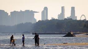 Vrije tijdsbeeld van mensen enjoysthe strand met centrale het districtsgebouwen van Singapore royalty-vrije stock afbeelding
