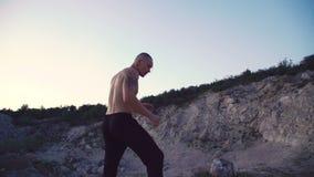 Vrije vechtersjogging op de ruwe rots en opleidings vrije strijd 4K stock footage