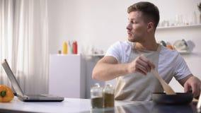 Vrijgezel die maaltijd in pan voorbereiden, recept lezen en uiteinden koken online, cursussen stock video