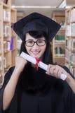 Vrijgezel met graduatietoga en een diploma Stock Afbeelding