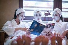 Vrijgezellinpartij in kuuroord, meisjes met de lezingstijdschrift van het gezichtsmasker Stock Foto's