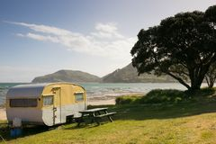 Vrijheid die in caravans bij een Oostkuststrand kamperen, Gisborne, het Noordeneiland, Nieuw Zeeland stock afbeeldingen