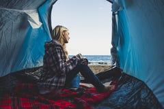 Vrijheid en alternatief uiterst klein huis of wild onafhankelijk vakantieconcept met de zitting van het blondemeisje op de tent e royalty-vrije stock afbeeldingen