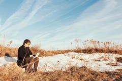 Vrijheid - Mens die laptop met behulp van openlucht in park met copyspace stock foto