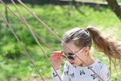 Vrijheid, onbezorgde levensstijl en pret Het maniermeisje in zonnebril geniet van slingerend op zonnige dag Weinig kind op schomm royalty-vrije stock fotografie