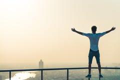 Vrijheid of succesconcept Witte mens die zich bij de rand van dak, het uitrekken zich wapens bevinden Zonsondergang op cityscape  stock afbeeldingen