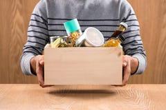Vrijwilliger met schenkingsdoos met levensmiddelen op houten achtergrond stock afbeeldingen