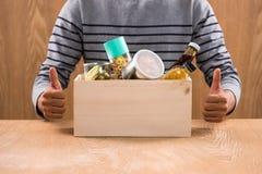 Vrijwilliger met schenkingsdoos met levensmiddelen op houten achtergrond stock foto