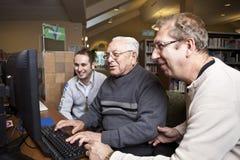 Vrijwilligers die een oudste onderwijzen hoe te om een computer te gebruiken Royalty-vrije Stock Afbeelding