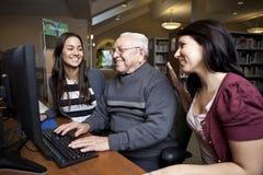 Vrijwilligers die een oudste onderwijzen hoe te om een computer te gebruiken Royalty-vrije Stock Afbeeldingen