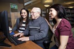 Vrijwilligers die een oudste onderwijzen hoe te om een computer te gebruiken Stock Fotografie