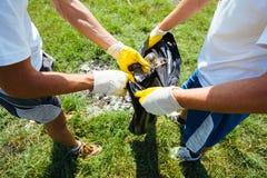 Vrijwilligers die huisvuil schoonmaken stock afbeelding