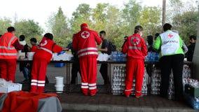 Vrijwilligers die van Rood kruis hulp voor vluchtelingen in Hongarije verdelen stock footage