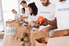 Vrijwilligers die voedsel en dranken zetten in zakken royalty-vrije stock foto