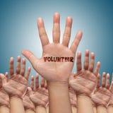 Vrijwilligers groep die handen opheft Stock Fotografie