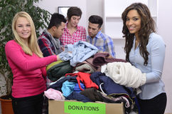 Vrijwilligers groep met kledingsschenking Stock Foto