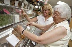 Vrijwilligers helpende oudste met haar die winkelt Stock Foto's