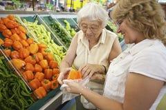 Vrijwilligers helpende oudste met haar die winkelt