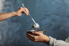 Vrijwilligers het zetten voedsel in kom van slechte vrouw op kleurenachtergrond, close-up royalty-vrije stock afbeeldingen