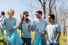 Vrijwilligers met vuilniszakken die parkgebied schoonmaken Stock Foto's