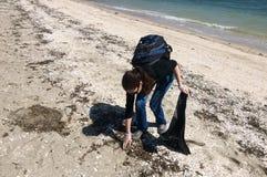 Vrijwilligers verzamelend huisvuil op strand Stock Afbeeldingen