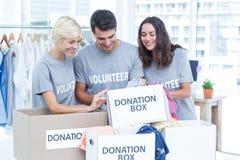 Vrijwilligersvrienden die een schenkingslijst controleren Royalty-vrije Stock Foto