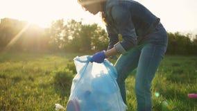 Vrijwilligersvrouw die huisvuil in een stadspark verzamelen De het plaatsen zon, heldere hoogtepunten, winderig weer Sociaal conc stock videobeelden