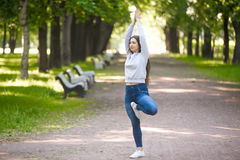 Vriksasana posture on park alley. Serene beautiful sporty young woman working out in park alley, doing stretching exercise, standing in asana Vrikshasana ( Stock Photo