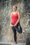 Vriksasana. Woman practicing yoga near waterfall. Tree Pose. Vriksasana Stock Image