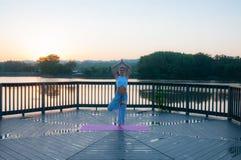 Vrikshasana pose. Young woman is doing yoga on the sunrise stock photo