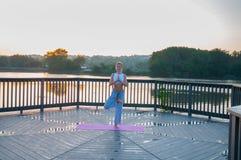 Vrikshasana pose. Young woman is doing yoga on the sunrise stock photos