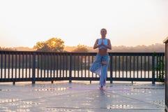 Vrikshasana pose. Young woman is doing yoga on the sunrise royalty free stock image