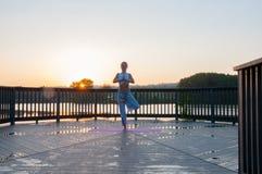 Vrikshasana pose. Young woman is doing yoga on the sunrise stock images