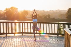 Vrikshasana stelt De jonge vrouw doet yoga op de zonsopgang stock foto