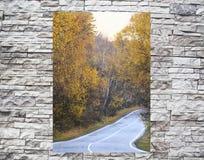 Vrillage de la route dans un hublot derrière un mur en pierre Photo stock
