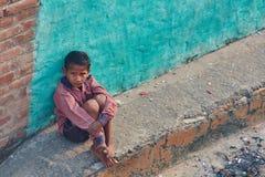 Vrindavan, 22-ое октября 2016: Ребенок сидя на улице, в Vr стоковая фотография