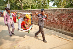 Vrindavan, 22 October 2016: Two people carry another person, at Royalty Free Stock Image