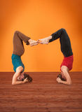 Vrisikasana Yoga. Two women perform Vrisikasana yoga posture on a wooden mat Stock Photo