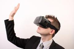 佩带VR虚拟现实Oculus裂口3D耳机的一个人的侧视图,接触某事用他的手,当他的胳膊被举 免版税库存照片