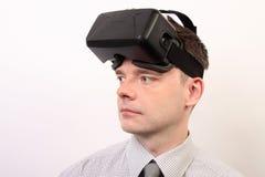 佩带VR虚拟现实Oculus裂口3D耳机,面孔的一个人的正面图看左 免版税库存图片