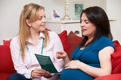 Vroedvrouw Looking At Leaflet met Zwangere Vrouw tijdens Huisbezoek stock foto's