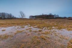 Vroeg de lentelandschap van weide en vulklei onder bewolkte hemel Royalty-vrije Stock Afbeelding