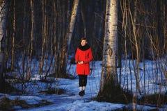 Vroeg de lenteportret van leuk aantrekkelijk ernstig jong meisje die met de donkere sjaal van de haarhitte en rood jasje aan zon  Royalty-vrije Stock Afbeelding