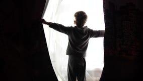 Vroeg in de ochtend opent het kind de gordijnen, gaan de zonstralen door het venster over Zonsopgang stock videobeelden