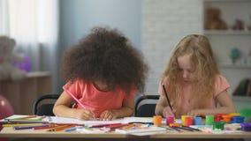 Vroeg onderwijs, twee multi-etnische vrouwelijke jonge geitjes die met kleurrijke potloden trekken stock videobeelden