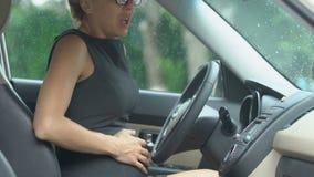Vroege geboorte, zwangere blonde vrouwelijke zitting in auto en het maken van diepe adem, pijn stock footage