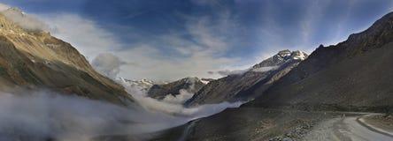 Vroege mistige ochtend op Lech Manali Highway: de wegpassen in wolken onder de hoogste bergen, worden de hellingen aangestoken do Stock Foto